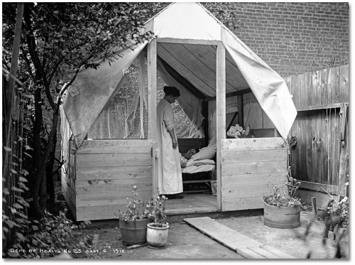 Nurse stands beside a man in a bed in a tent.