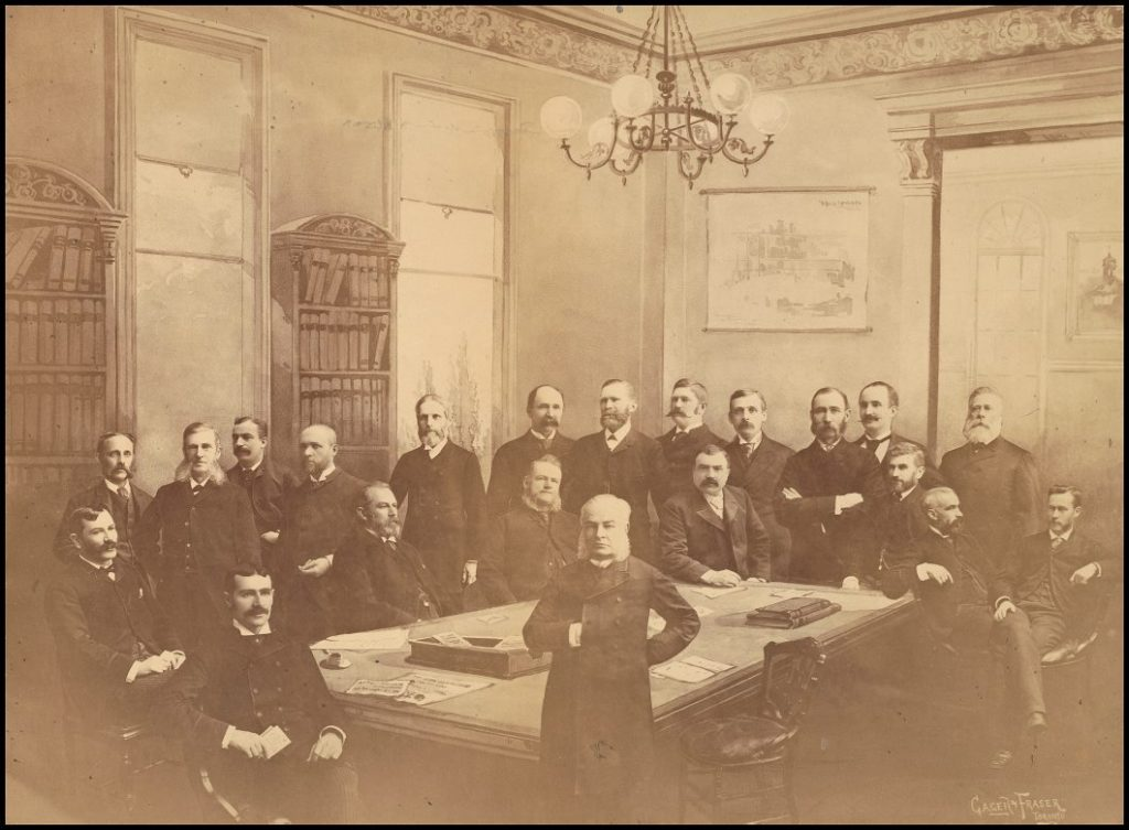 Men in dark suits standing around a table.