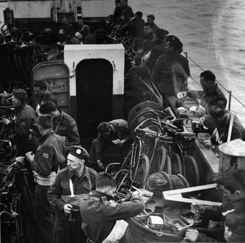 Soldiers are eating a meal while standing on the narrow deck of a troop carrier, surrounded by tightly packed bicycles. They are balancing their dishes on bicycles, railings, spools of rope, and other items on deck. They are eating out of rectangular metal containers.
