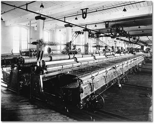 Long automatic looms on a large factory floor lit by big windows.