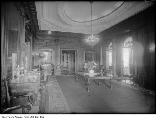 Dining room with heavy wooden furniture and large chandelier.