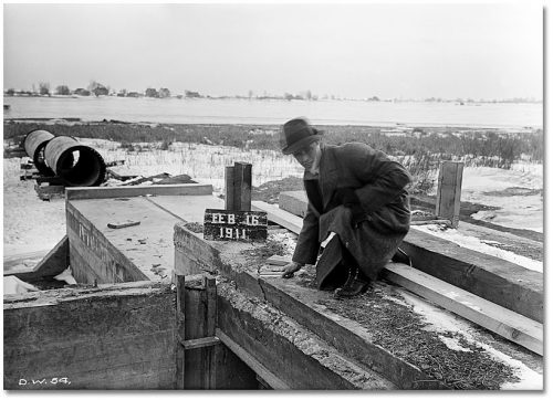 Man in winter coat squats on low block concrete structure and holds ruler against a large crack.
