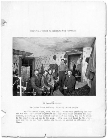 Page of book with photograph showing six men sitting on beds in small, low-ceilinged bedroom.