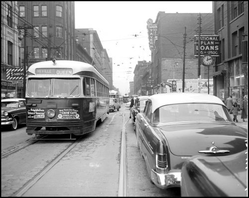 A streetcar with a rounded roof on one side of the street and large 1950s cars on the other.