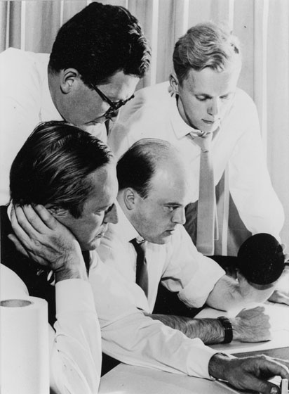 Group of white male architects in white shirts and ties gathered around desk