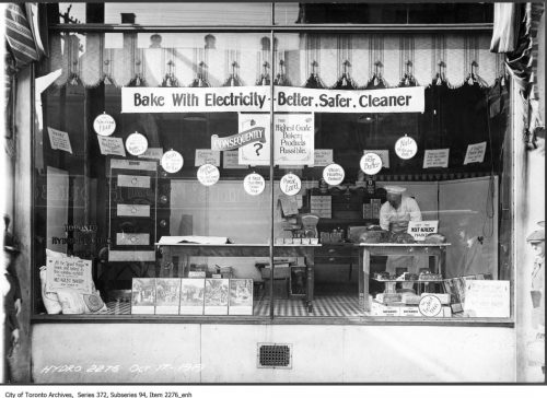"""Shop window displaying stoves with the slogan """"Bake with electricity, better, safer, cleaner."""""""