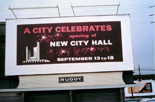 Billboard advertising City Hall opening celebrations, showing City Hall and fireworks