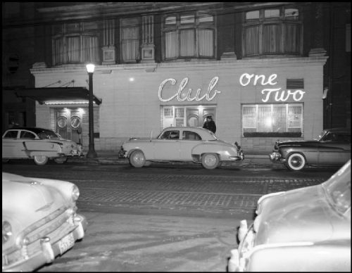 "Cars parked in front of a wide building with ""Club One Two"" spelled out in lights on the front."