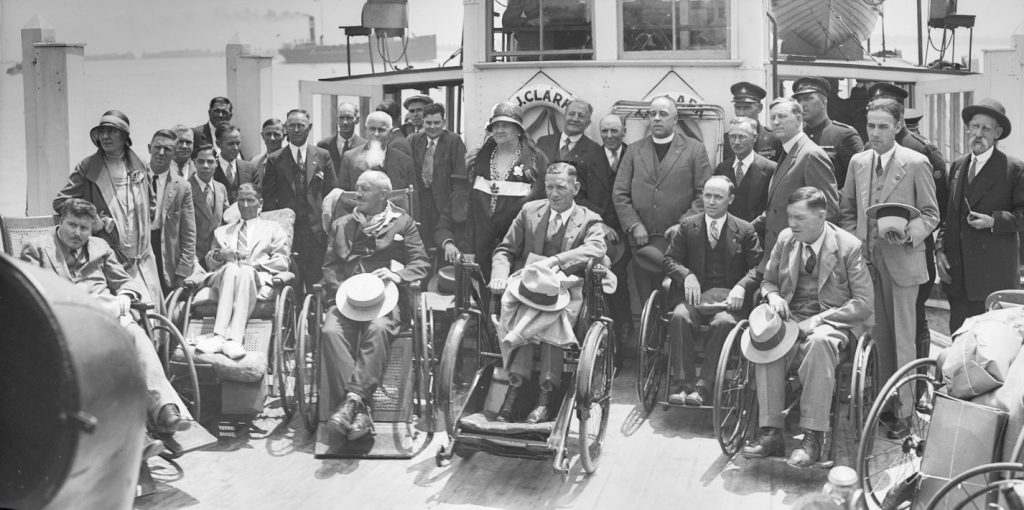 Group of men in wheelchairs or standing on the deck of a ferry boat.