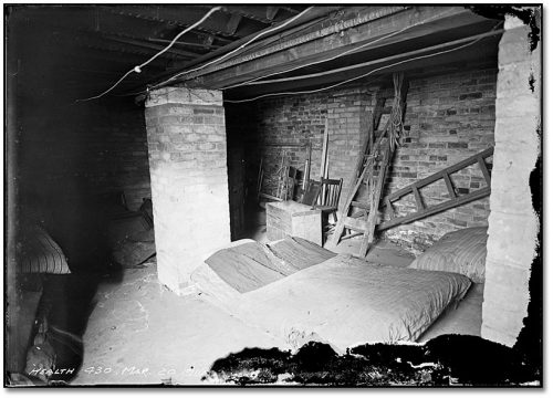A mattress lies on the floor in an unfinished brick basement.