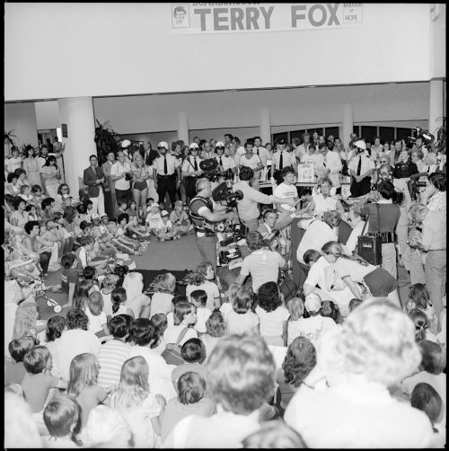 A picture of Terry Fox inside Scarborough Civic Centre surrounded by a huge crowd