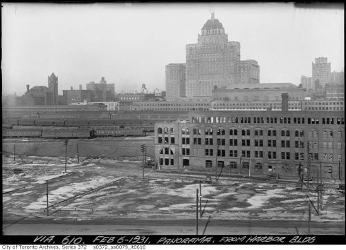 A abandoned brick factory, train tracks and trains, and the tall, broad Royal York Hotel in the background.