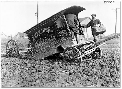 Men in muddy boots unloading baskets of bread from a mud-covered delivery wagon that has come off its wheels.