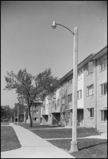 Concrete lamp post outside a row of 1950s townhouses.