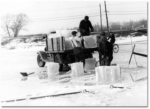 On a frozen lake, men use metal tongs to lift two-foot-wide cubes of ice onto the back of a truck.