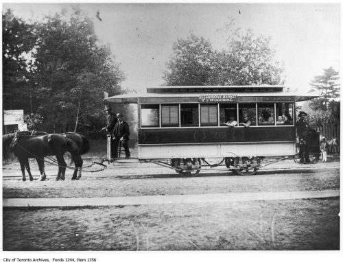 Small streetcar pulled by two horses.