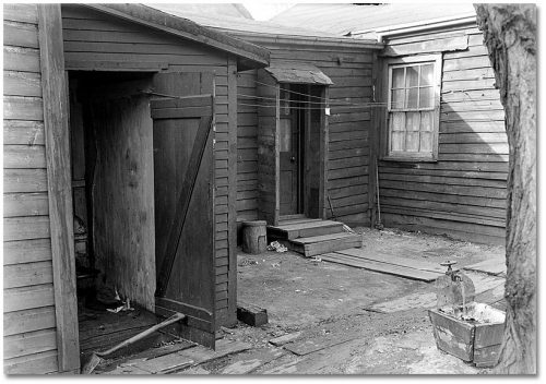 Courtyard surrounded by small wooden houses, with water running from an outdoor tap into a square wooden box.