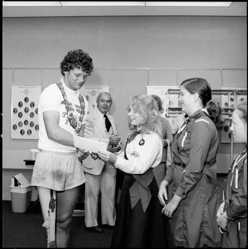 A picture of Terry Fox receiving gifts from two girl guides