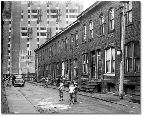 Children play on a narrow street lined with old brick houses, while a highrise takes up the background.