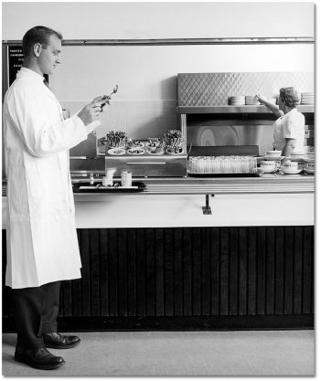 Standing in front of a cafeteria food line, a man in a white lab coat examines a spoon.