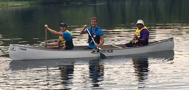 Three people on the water in a canoe