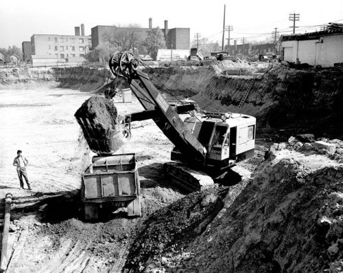 Steam shovel works in large excavation.