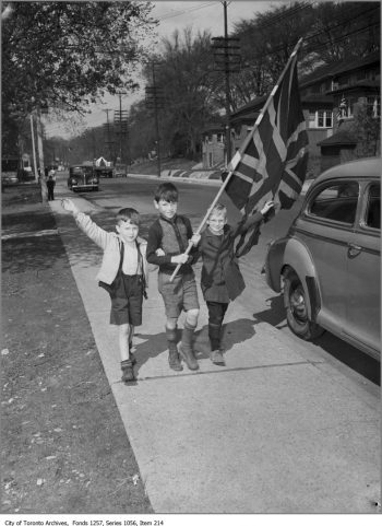 Small boys walk down a sidewalk, waving a Union Jack.
