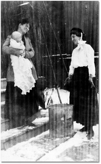 Two women, one holding a baby, stand outside looking at a garbage can.