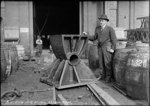 Man standing beside cast iron piece shaped like an hourglass coming up to his chest.