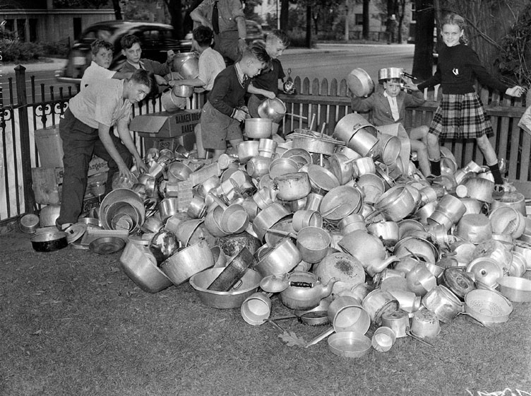 Children with a large heap of pots and pans.