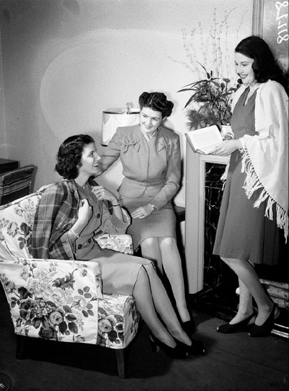 Three women are gathered in a living room. They are all wearing skirts, but one wears a jacket draped over her shoulders, the second wears a suit with jacket fastened in front, and a third has a shawl over her dress.