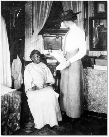 A white woman stands beside a Black woman sitting in a chair.