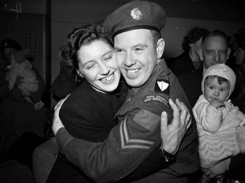 A soldier and a woman embrace cheek to cheek. A baby looks on from the side.