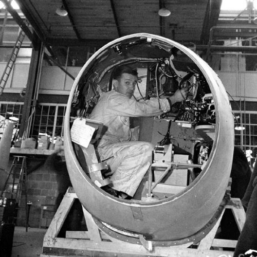 A man works on wiring while squatting in an airplane's oval cockpit.