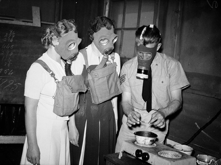 A soldier cooks something in a small bowl on a hotplate. Two women in civilian clothes watch him. All are wearing gas masks.