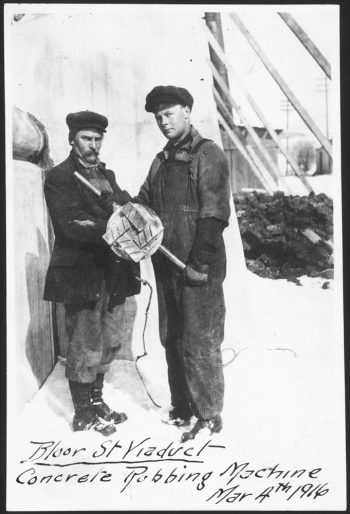 Two men holding a round piece of wood about a foot across.