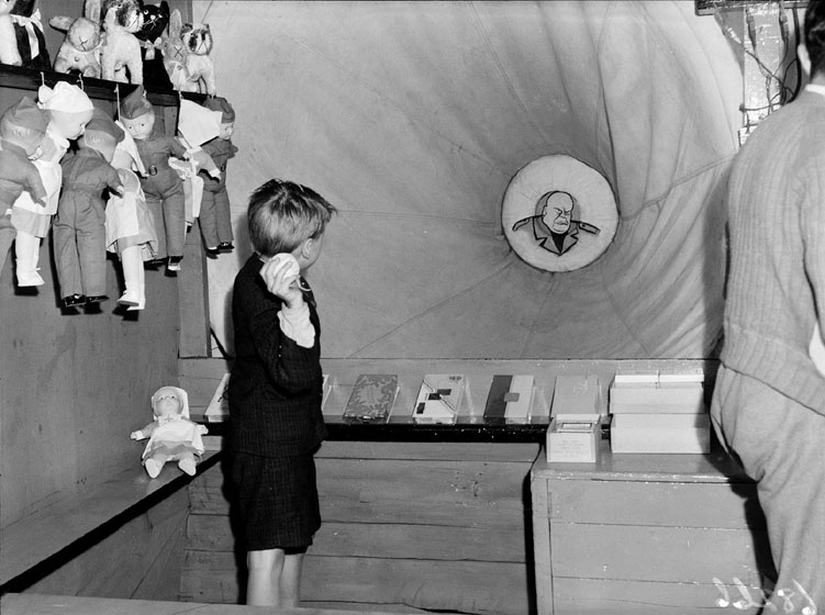 A boy throws a ball at a target showing a caricature of Mussolini. Prizes are lined up in front of the boy and also hanging on the wall at his side.