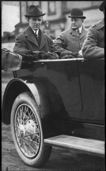 Two men in hats in the back of an open-topped car.