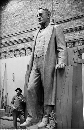 Sculptor stands at foot of large stone man.