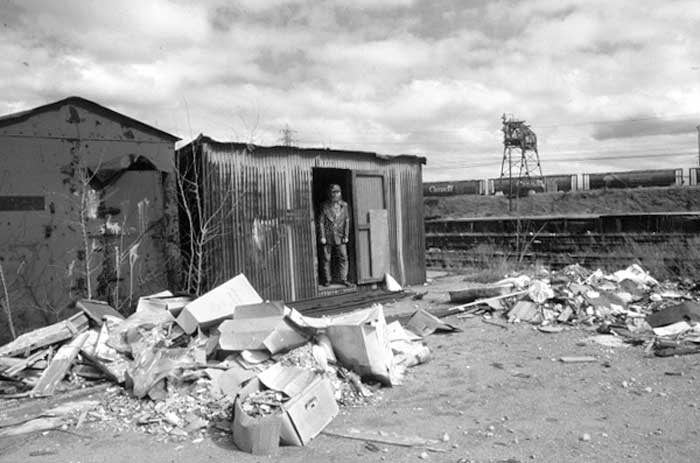 Man stands in the door of a corrugated metal shack, garbage and broken boxes are lying around on the ground outside