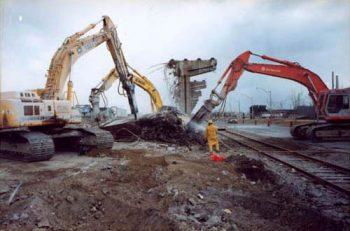 Large jackhammer machines break up a concrete slab on the ground