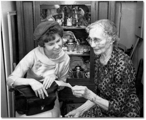 A young woman in a hat and an elderly woman in a patterned dress look together at a photograph.