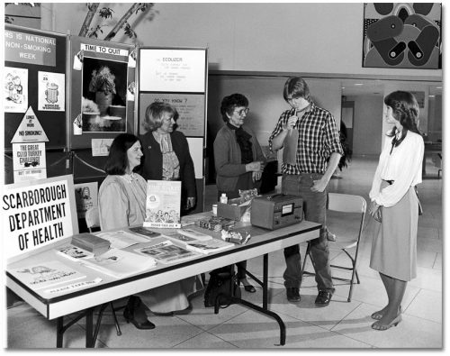 In front of a display of anti-smoking posters and brochures, a young man breathes into a device while people watch.