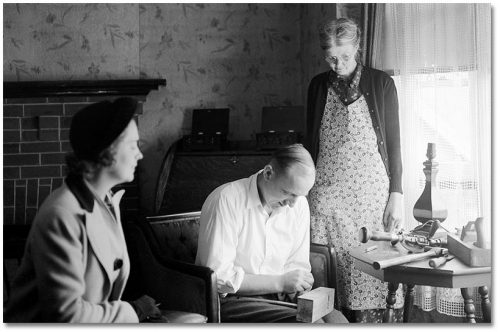 A nurse sits with an elderly woman wearing an apron, and an elderly man who seems to be doing some sort of woodworking with a block of wood in his lap.