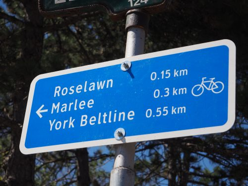 Photograph of a small blue wayfinding sign directing cyclists to nearby roads and trails