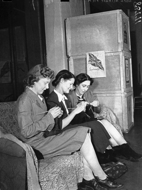 Dorothy McCabe, Queenie Edward, and Edith Allen knitting in a Red Cross workroom.