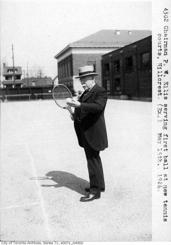Man in suit holding tennis raquet.