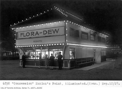 People line up at a two-storey wooden concession building that is outlined on all corners with lights.