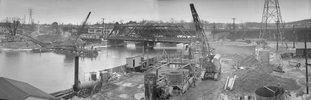 Construction on a pier in a river, with construction equipment and concrete forms, and a steel bridge in the background.