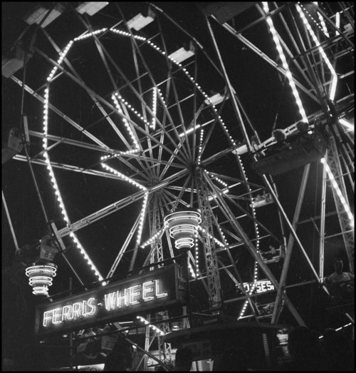Ferris wheel with wheel and spokes outlined in lights.